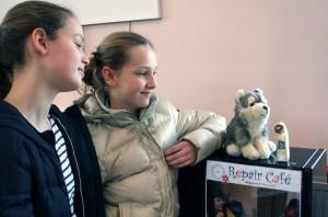 Twee jonge bezoeksters genoten zaterdag van hun reparatie-moment: het beeldje werd gelijmd en het knuffelbeest geheeld door vrijwilligers van Repair Café Oegstgeest.   Foto Frans Malten
