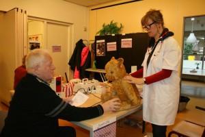 Heer A. de Vink houdt de oude teddybeer vast terwijl 'poppendokter' Heleen de Visser de oren er weer aannaait, tijdens het Repair Café van zaterdag 25 januari in de Gevers-Deutz Terweeschool. Foto PR