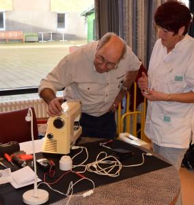 Een medewerkster van de Marente-huizen buigt zich met vrijwillig reparateur Cees Juffermans over een stilgevallen naaimachine